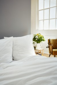 white bed linen fresh flowers on night stand industrial loft